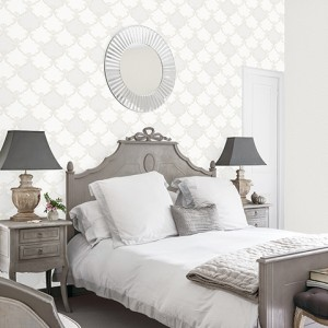 Circular mirror above double bed in rom with muted greys and whites